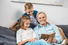 Family using laptopgrandfather and grandchildren reading book. Happy grandfather and grandchildren reading book while sitting on sofa at home stock photography