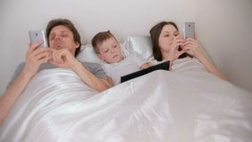 Family is using mobile devices phones and tablet lying in the bed in the morning. Family is using mobile devices phones and tablet lying in the bed in the stock footage
