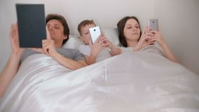 Family is using mobile devices phones and tablet lying in the bed in the morning. Family is using mobile devices phones and tablet lying in the bed in the stock video footage