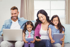 Family using modern technologies while sitting on sofa Stock Photo