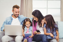 Family using modern technologies on sofa Royalty Free Stock Image
