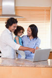 Family using notebook in the kitchen together Stock Photo
