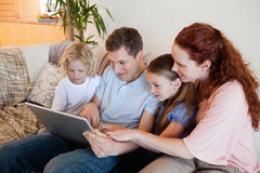 Family using notebook on the sofa Stock Images