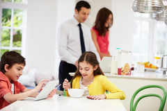 Family Using Tablet At Breakfast Table. Family Using Digital Devices At Breakfast Table Stock Photos