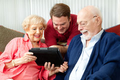 Family Using Tablet Computer. Adult son teaching his parents to use their new tablet pc computer royalty free stock photos