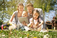 Family using tablet outdoors. Happy family using tablet outdoors, sitting on the green grass royalty free stock photos