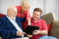 Family Using Tablet PC. Adult son and elderly parents using their tablet PC at home royalty free stock photo