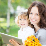 Family using tablet PC outdoors Stock Photos