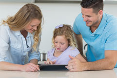 Family using tablet PC at table Royalty Free Stock Image