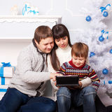 Family using tablet together on winter holidays Royalty Free Stock Photos