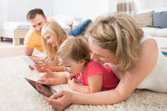 Family using tablets lying on carpet Stock Photos
