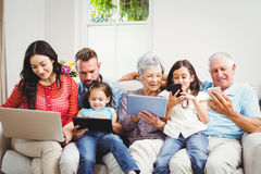 Family using technologies while sitting in sofa Royalty Free Stock Photo
