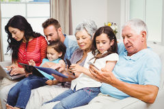 Family using technologies while sitting on sofa Stock Photos