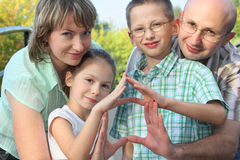 Family is using their hands to represent home. Dad, mom, son and daughter is using their hands to represent home. focus on son's face Stock Photos