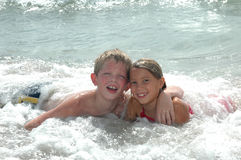 Family Vacation. Happy Cousins hang together on vacation on the beach. Boy and girl laying in the ocean waves looking at the camera Royalty Free Stock Photography