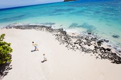 Family at vacation. Above view of gorgeous rocky white sand beach with turquoise lagoon and family of two, father and son, walking and enjoying family vacation Royalty Free Stock Photos