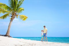 Family on vacation. Beautiful family of two, father and son, standing together at the beach with palm tree in the background enjoying summer vacation, white sand Stock Photo