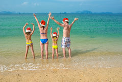 Family vacation on Christmas and New Year holidays, happy parents and children in santa hats have fun on beach Royalty Free Stock Photos