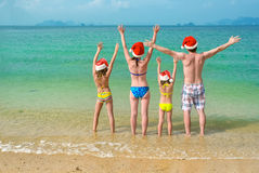Family vacation on Christmas and New Year holidays, happy parents and children in santa hats have fun on beach Royalty Free Stock Photo