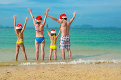 Family vacation on Christmas and New Year holidays, happy parents and children in santa hats have fun on beach Stock Photography