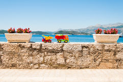 Family vacation concept. Brightly colored kids toy trucks with sea view in the background Royalty Free Stock Photo