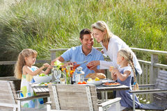 Family on vacation eating outdoors. Family on vacation eating lunch outdoors on decking royalty free stock images