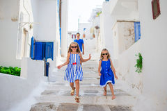 Family vacation in Europe. Father and kids at street of typical greek traditional village on Mykonos Island, in Greece Stock Photos
