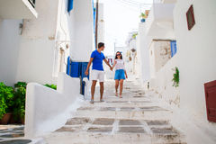 Family vacation in Europe. Happy couple at street of typical greek traditional village on Mykonos Island, in Greece Stock Photos