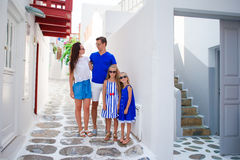 Family vacation in Europe. Parents and kids at street of typical greek traditional village on Mykonos Island, in Greece Royalty Free Stock Images