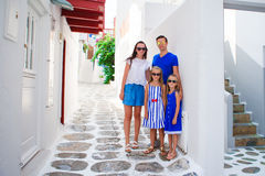 Family vacation in Europe. Parents and kids at street of typical greek traditional village on Mykonos Island, in Greece Royalty Free Stock Photography