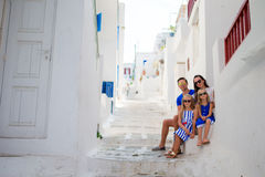 Family vacation in Europe. Parents and kids at street of typical greek traditional village on Mykonos Island, in Greece Stock Photography