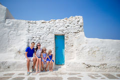 Family vacation in Europe. Parents and kids at street of typical greek traditional village on Mykonos Island, in Greece Royalty Free Stock Photos