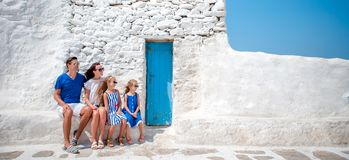 Family having fun outdoors on Mykonos streets. Family vacation in Europe. Parents and kids at street of typical greek traditional village with white walls and Stock Photos