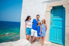Family vacation in Europe. Parents and kids at street of typical greek traditional village with white walls and colorful. Family having fun outdoors on Mykonos Royalty Free Stock Images