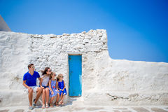 Family vacation in Europe. Parents and kids at street of typical greek traditional village with white walls and colorful Stock Photos