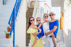 Family vacation in Europe. Parents and kids at street of typical greek traditional village with white walls and colorful Royalty Free Stock Photo