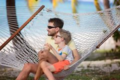Family at vacation. Family of two, father and son, enjoying beautiful tropical island relaxing in hammock, family vacation concept Royalty Free Stock Photo
