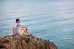 Family at vacation. Family of two, father and son, enjoying sunset together sitting at the rock at anguilla island, caribbean, copy space on right Stock Images