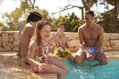 Family On Vacation Having Fun By Outdoor Pool Royalty Free Stock Image