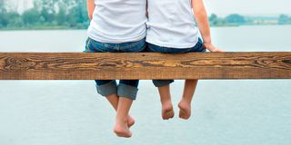 Two brothers swung their legs from the wooden pier .Family vacation on the lake. royalty free stock photo