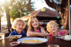 Family vacation lunch. Kids in beach restaurant. Family eating lunch on tropical beach. Kids in outdoor restaurant of exotic resort in Asia. Asian food for stock photography