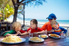 Family vacation lunch. Kids in beach restaurant. Family eating lunch on tropical beach. Kids in outdoor restaurant of exotic resort in Asia. Asian food for royalty free stock image