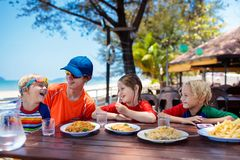 Family vacation lunch. Kids in beach restaurant. Family eating lunch on tropical beach. Kids in outdoor restaurant of exotic resort in Asia. Asian food for stock images