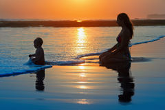 Family vacation. Mother with child on sunset beach stock image