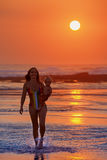 Family vacation. Mother with child walk on sunset beach. Royalty Free Stock Images