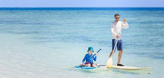 Family on vacation. Panorama of happy family of two, father and son, in rashguards enjoying stand up paddleboarding, healthy family activity during summer Royalty Free Stock Photo