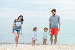 Family vacation parents and children on the sea shore summer day Royalty Free Stock Images