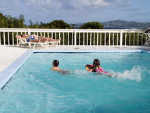 Family Vacation By Pool. Brother and sister swimming in a clear, blue pool while their parents relax on chairs in the sun with the Caribbean Island of St. Croix Stock Photography