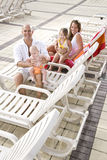 Family vacation, relax on pool deck lounge chairs. Young family on vacation, relaxing on pool deck lounge chairs Stock Image