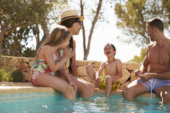 Family On Vacation Relaxing By Outdoor Pool Stock Image